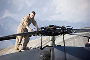 Airfield Prints - An Airman Checks The Main Rotors Of An Print by Stocktrek Images