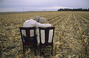 Benches Photos - An Elderly Couple Embrace by Joel Sartore
