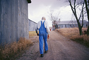 Dirt Roads Photo Prints - An Elderly Farmer In Overalls Walks Print by Joel Sartore