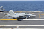 Carrier Posters - An Fa-18c Hornet Lands Aboard Uss Poster by Stocktrek Images
