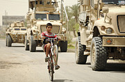 Tricks Posters - An Iraqi Boy Rides His Bike Past A U.s Poster by Stocktrek Images
