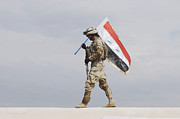 Uniforms Posters - An Iraqi Soldier Carries The Iraqi Flag Poster by Stocktrek Images