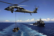 Boats At Dock Photo Posters - An Mh-60s Knighthawk Transports Cargo Poster by Stocktrek Images