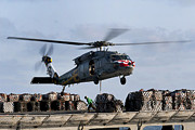 Pallet Framed Prints - An Mh-60s Sea Hawk Lifts Cargo Framed Print by Stocktrek Images
