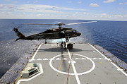 Royal Australian Navy Prints - An Sh-60f Sea Hawk Helicopter Lowers Print by Stocktrek Images