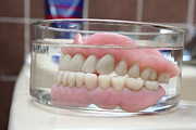 Biting Posters - Artificial denture in a glass  Poster by Kristian Peetz
