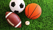 Game Posters - Assortment of sport balls on grass Poster by Sandra Cunningham