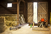 Stored Prints - Barn with hay bales and farm equipment Print by Elena Elisseeva