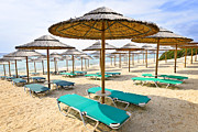 Empty Chairs Art - Beach umbrellas on sandy seashore by Elena Elisseeva