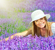 Enjoying Prints - Beautiful happy female lying down on lavender field Print by Anna Omelchenko
