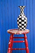 Old Vase Posters - Blach and white vase on stool against blue wall Poster by Garry Gay