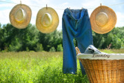 Basket Prints - Blue jeans and straw hats on clothesline Print by Sandra Cunningham