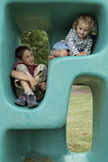 Kneeling Prints - Boy and girl playing in plastic cube Print by Sami Sarkis