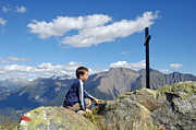 Alp Photos - Boy on mountain top looking at cross by Matthias Hauser