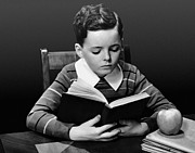 Desk Photo Prints - Boy Reading Book At Desk Print by George Marks