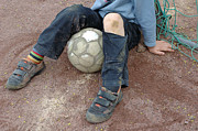 Knees Prints - Boy with soccer ball sitting on dirty field Print by Matthias Hauser