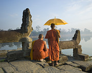 Religious Dress Prints - Buddhist Monks Standing Next To Stone Carvings Print by Martin Puddy
