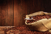 Mocha Acrylic Prints - Burlap sack of coffee beans against dark wood Acrylic Print by Sandra Cunningham