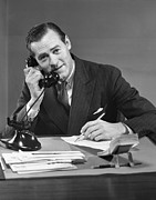 Desk Photo Prints - Businessman At Desk On Telephone Print by George Marks