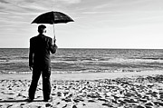 Anticipation Posters - Businessman with umbrella on beach Poster by Sami Sarkis