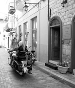 Neo-classical Framed Prints - BW Sexy Girl Riding on Motorcycle with Handsome Bike Rider Speed Stone Paved Street Nafplion Greece Framed Print by John A Shiron