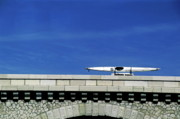 Sami Sarkis - Car carrying a kayak on its roof while travelling on the bridge