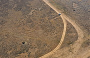 Dirt Road Posters - Car on dirt road in desert Poster by Sami Sarkis