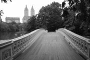 New York Photo Framed Prints - Central Park Bow Bridge with The San Remo Framed Print by Christopher Kirby