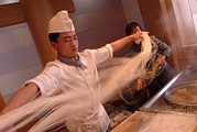 Chef Stretches Dough As He Makes Fresh Print by Richard Nowitz