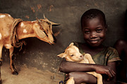 Goats Prints - Child Holding A Kid Print by Mauro Fermariello