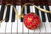 Ribbon Framed Prints - Christmas ornament on piano keys Framed Print by Garry Gay