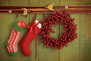 December Prints - Christmas stockings and wreath hanging on  wall Print by Sandra Cunningham