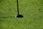 Golf Flag Posters - Close View Of A Flag Pole In A Hole Poster by Todd Gipstein