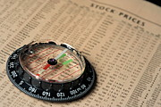 Sami Sarkis Photos - Compass on stockmarket cotation in newspaper by Sami Sarkis