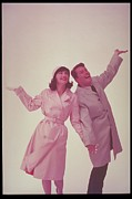 Trench Coat Framed Prints - Couple In Raincoat With Hands Up, 1962 Framed Print by Archive Holdings Inc.