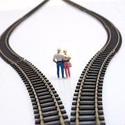 Figures Metal Prints - Couple two figurines between two tracks leading into different directions symbolic image for making decisions Metal Print by Bernard Jaubert