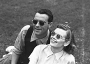 Sweater Vest Framed Prints - Couple Wearing Sunglasses Sitting On Grass, (b&w) Framed Print by George Marks
