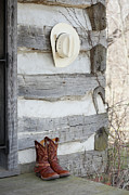 Log Cabin Prints - Cowboy Boots And Hat Outside Of Log Cabin Print by Vstock LLC