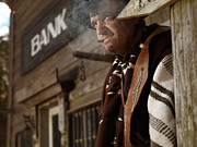 Poncho Photo Framed Prints - Cowboy Smoking a Cigar Outside of a Bank Building Framed Print by Oleksiy Maksymenko