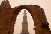 Qutb Posters - Cross section of the Qutub Minar framed within an archway in foggy weather Poster by Ashish Agarwal