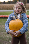 Heavy Weather Prints - Cute little girl carrying large pumpkin Print by Purcell Pictures