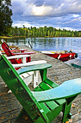 Seats Photo Prints - Deck chairs on dock at lake Print by Elena Elisseeva