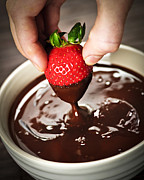 Creamy Posters - Dipping strawberry in chocolate Poster by Elena Elisseeva
