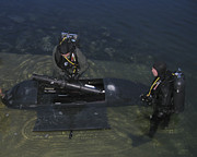 Diving Suit Prints - Divers Load Equipment Into Their Seal Print by Michael Wood