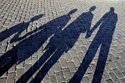 Four People Posters - Family of four casting shadows on cobbled stone street Poster by Sami Sarkis