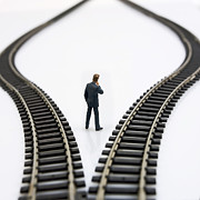 Rear Prints - Figurine between two tracks leading into different directions  symbolic image for making decisions Print by Bernard Jaubert