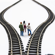 Thoughtful Photos - Figurines between two tracks leading into different directions symbolic image for making decisions. by Bernard Jaubert