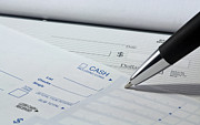 Banking Photo Posters - Filling out deposit slip Poster by Blink Images