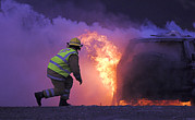 Bravery Prints - Firefighter Tackling A Burning Car Print by Duncan Shaw