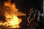 Protective Framed Prints - Firefighters Extinguish A Simulated Framed Print by Stocktrek Images